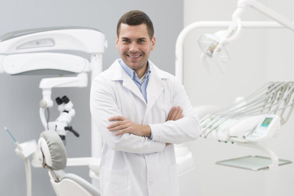 dentiste dans son cabinet médical souriant